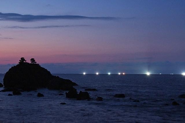 夜の海に灯る漁火